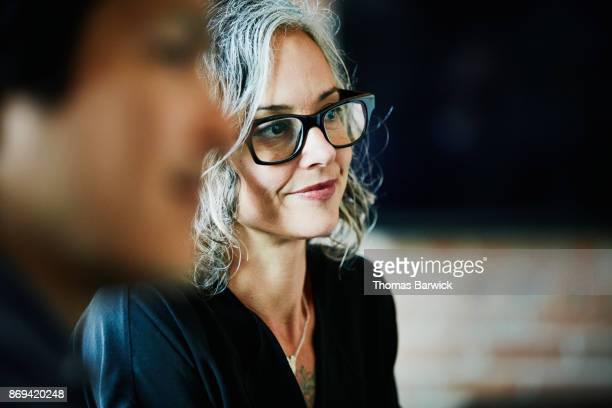 smiling businesswoman listening during team meeting in office conference room - luisteren stockfoto's en -beelden