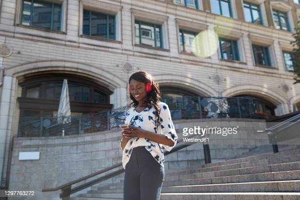 smiling businesswoman listening music while walking on staircase in city - commuter stock pictures, royalty-free photos & images