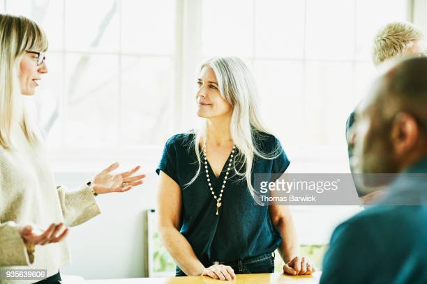 smiling businesswoman listening to colleague during meeting in office conference room - bottle green stock pictures, royalty-free photos & images