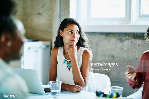 smiling businesswoman listening to coworker during meeting in conference room - black hair stock pictures, royalty-free photos & images