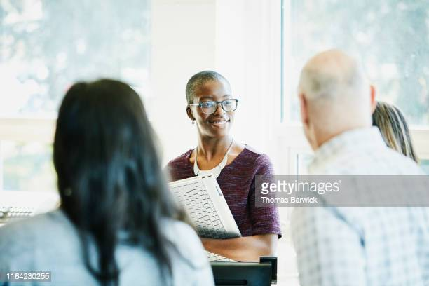 smiling businesswoman listening to coworkers during informal meeting in office - chance stock pictures, royalty-free photos & images