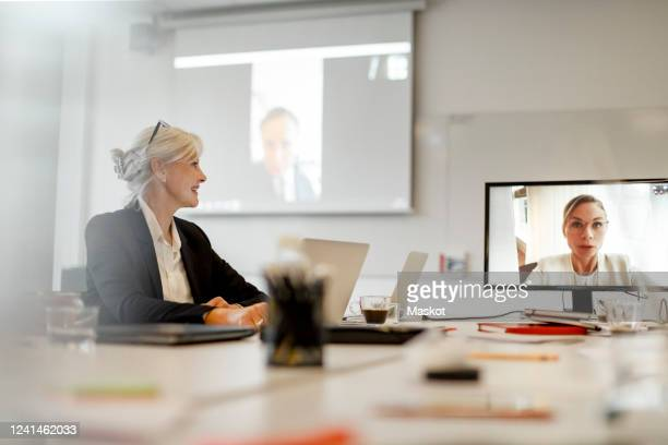 smiling businesswoman listening to female professional through video conference in board room at office - テレビ会議 ストックフォトと画像