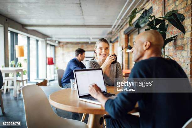 Smiling businesswoman looking at colleague in cafeteria