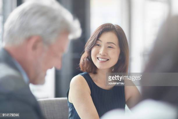 smiling businesswoman looking at colleague - differential focus stock pictures, royalty-free photos & images