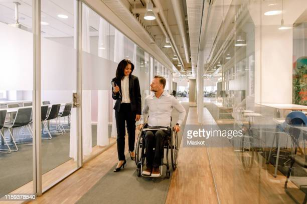 smiling businesswoman looking at disabled colleague sitting on wheelchair in corridor at work place - differing abilities fotografías e imágenes de stock
