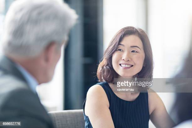 smiling businesswoman looking at mature coworker - asian 50 to 55 years old woman stock photos and pictures