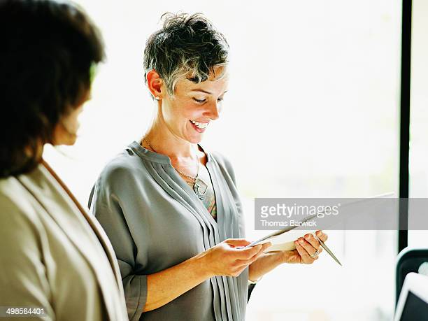 Smiling businesswoman looking at notepad in office