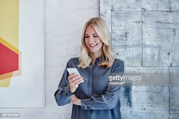 smiling businesswoman looking at smartphone - looking down her blouse stock photos and pictures