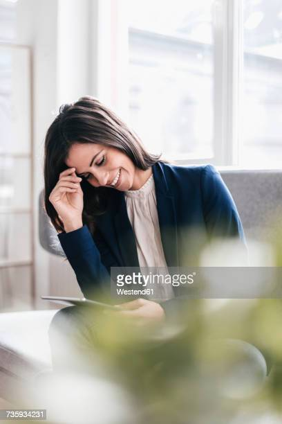 Smiling businesswoman looking at tablet on couch
