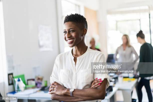 Smiling businesswoman looking away at office