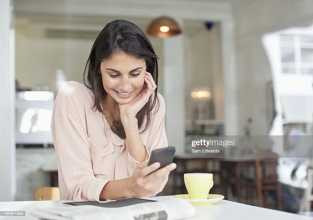 Smiling businesswoman looking down at cell phone in cafe window : Stock Photo