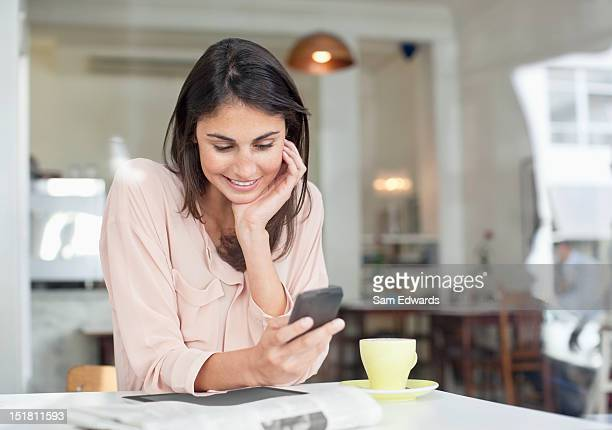 smiling businesswoman looking down at cell phone in cafe window - brown hair stock pictures, royalty-free photos & images