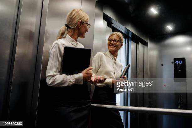 smiling businesswoman looking in mirror in elevator - mirror stock pictures, royalty-free photos & images