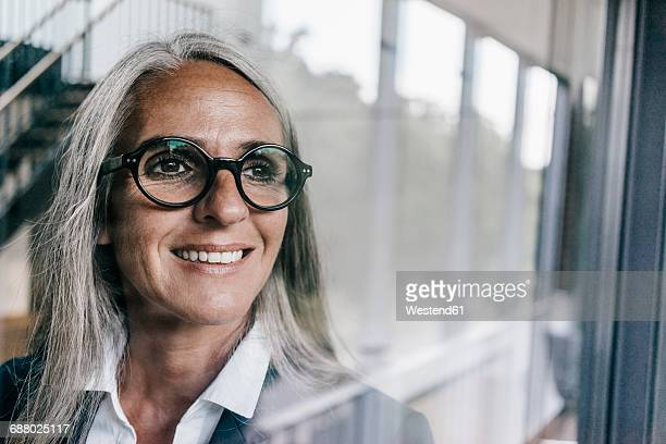 smiling businesswoman looking out of window - reflexo efeito de luz - fotografias e filmes do acervo