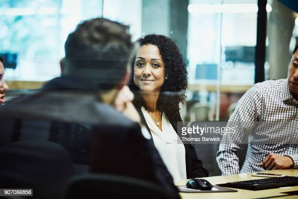 Smiling businesswoman meeting with clients in office conference room