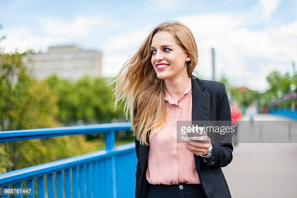Smiling businesswoman on a bridge with smartphone