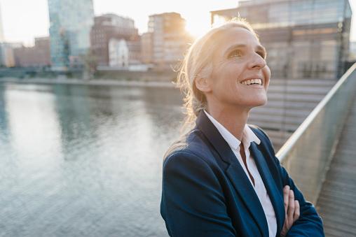 Smiling businesswoman on bridge looking up - gettyimageskorea