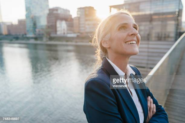 Smiling businesswoman on bridge looking up