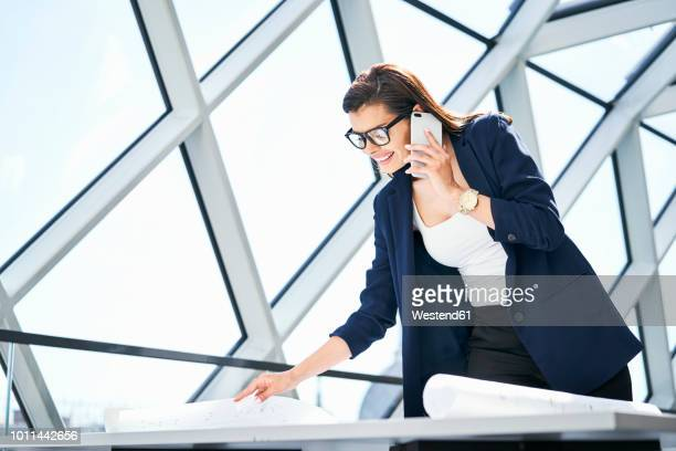 smiling businesswoman on cell phone looking at plan in office - 女性建築家 ストックフォトと画像