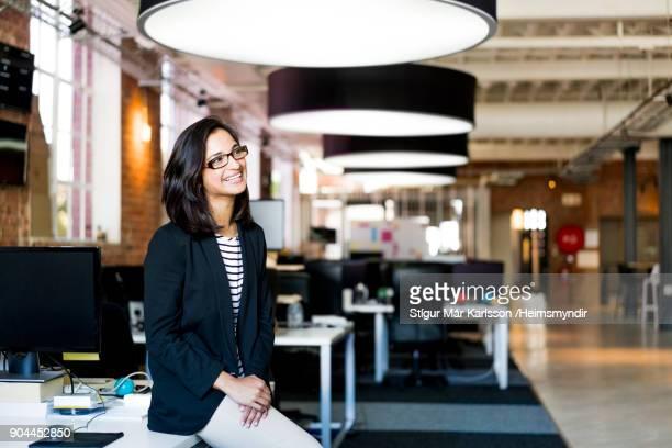 empresária sorridente na secretária no escritório - plano americano - fotografias e filmes do acervo
