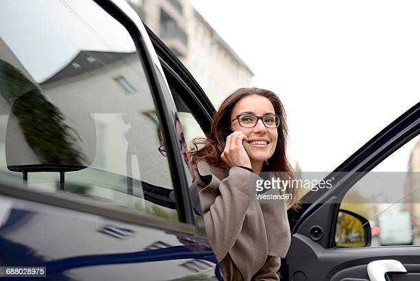 Smiling businesswoman on the phone getting out of car