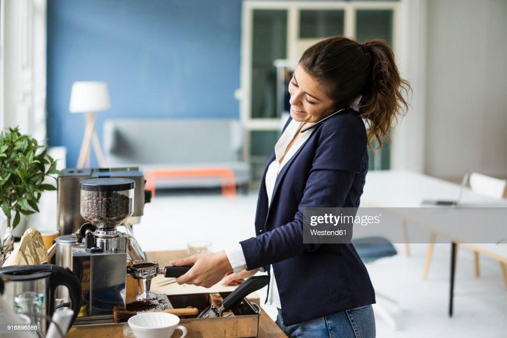 Smiling businesswoman on the phone preparing espresso with espresso machine in a loft : Stock Photo