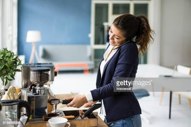 Smiling businesswoman on the phone preparing espresso with espresso machine in a loft