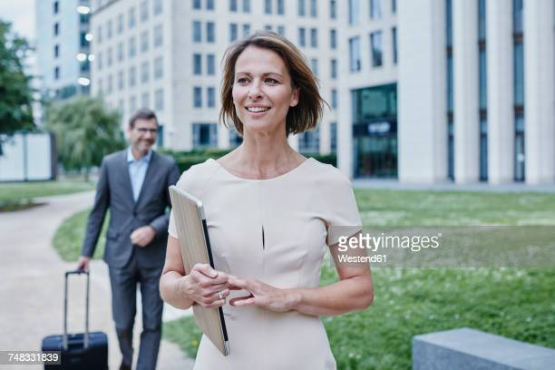 Smiling businesswoman outdoors with laptop and businessman in background