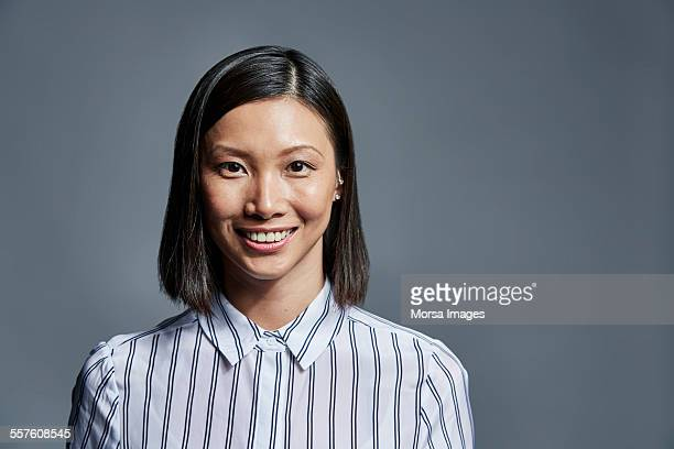 smiling businesswoman over gray background - primo piano del volto foto e immagini stock