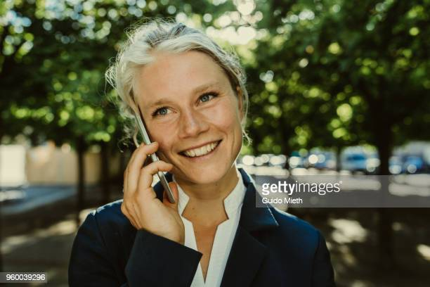 Smiling businesswoman phoning in a park.