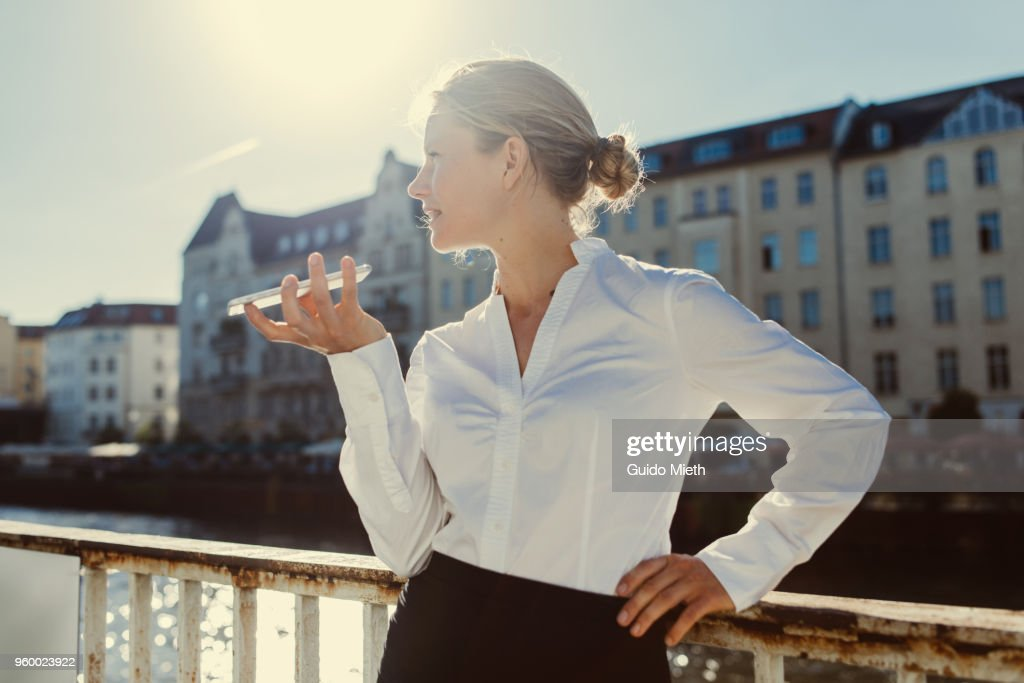 Smiling businesswoman phoning in front of a river. : Stock-Foto