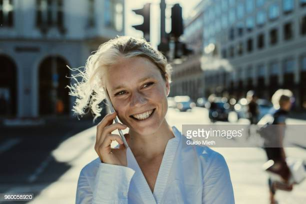 Smiling businesswoman phoning in the street.