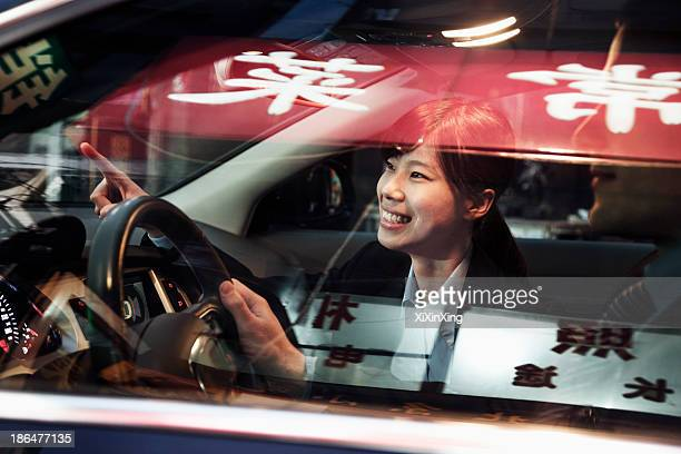 Smiling businesswoman pointing out of the car while driving through Beijing at night