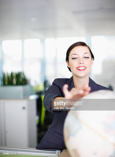 Smiling businesswoman reaching for globe