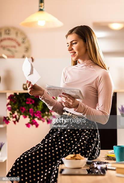 Smiling businesswoman reading mail letters in the office.