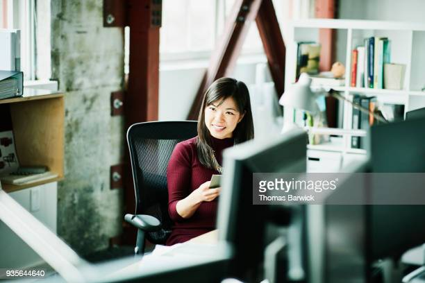 Smiling businesswoman reading project brief at workstation in office