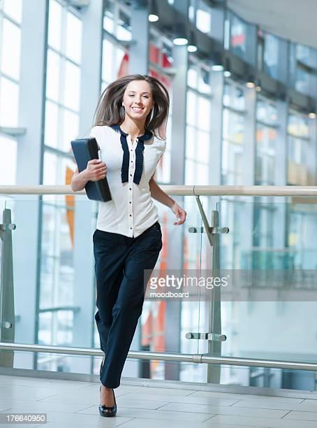 Smiling businesswoman runs towards camera