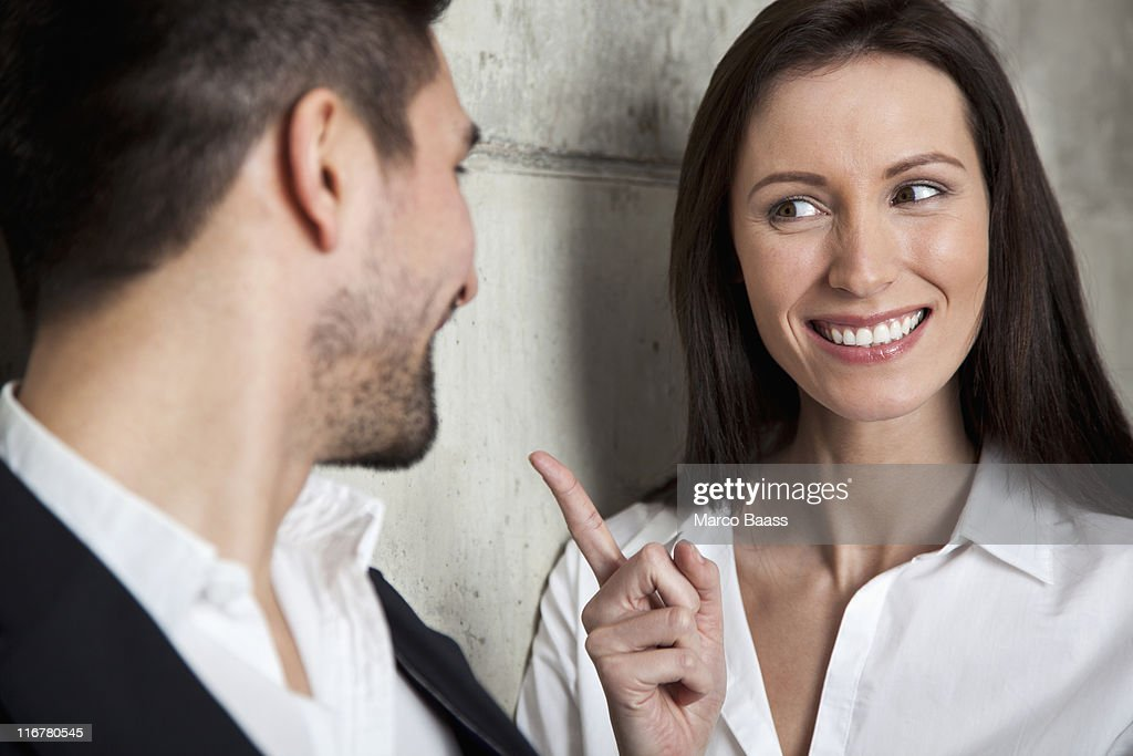 A smiling businesswoman scolding a businessman : Stock Photo