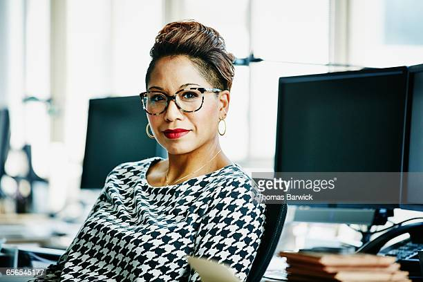 smiling businesswoman seated at office workstation - sexo feminino - fotografias e filmes do acervo