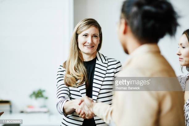 smiling businesswoman shaking hands with client before meeting - employee engagement stock pictures, royalty-free photos & images