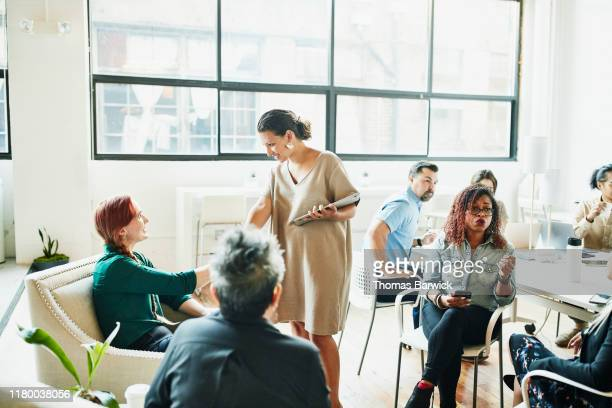 smiling businesswoman shaking hands with client before team meeting in coworking space - employee engagement stock pictures, royalty-free photos & images