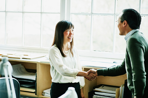 Smiling businesswoman shaking hands with client in design studio - gettyimageskorea