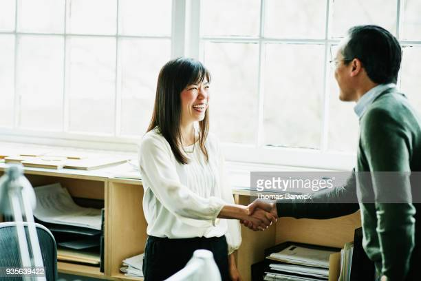 smiling businesswoman shaking hands with client in design studio - finance and economy stock pictures, royalty-free photos & images