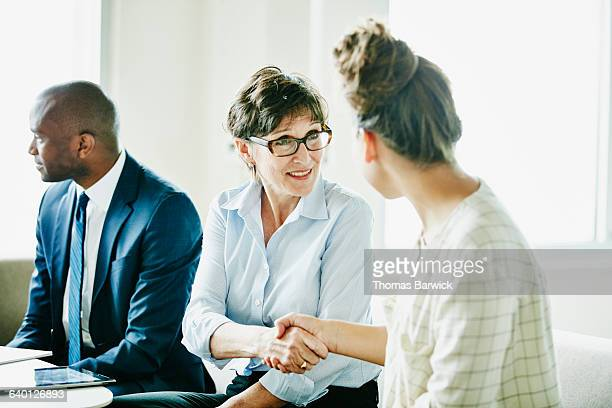 Smiling businesswoman shaking hands with colleague