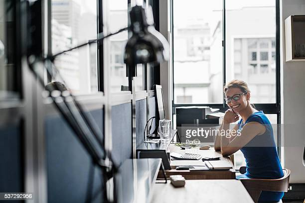Smiling businesswoman sitting at computer desk