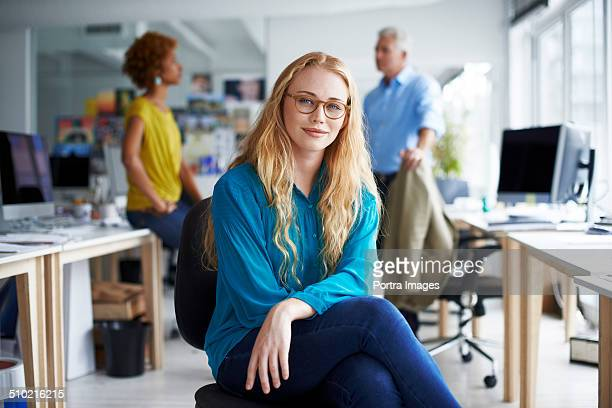 smiling businesswoman sitting at creative office - onscherpe achtergrond stockfoto's en -beelden