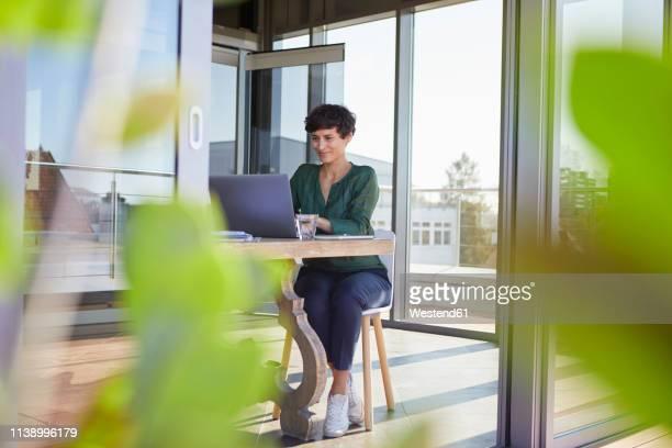 smiling businesswoman sitting at table using laptop - freischaffender stock-fotos und bilder