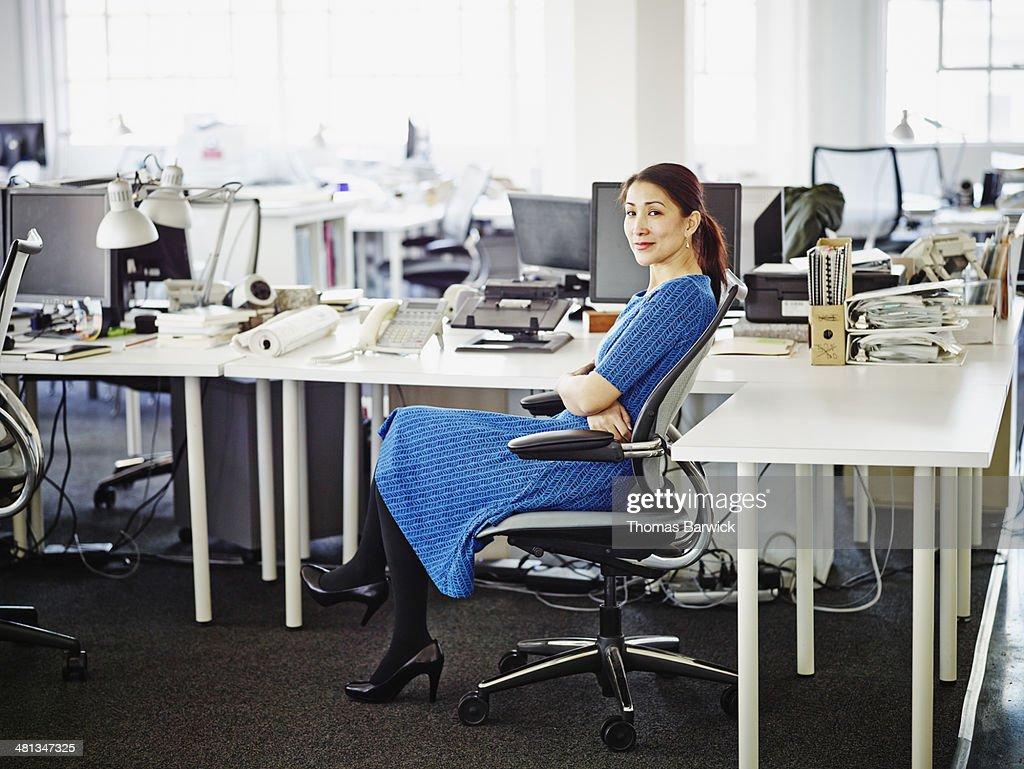 Smiling businesswoman sitting at workstation : Stock Photo