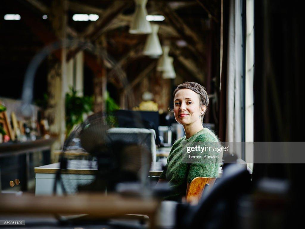 Smiling businesswoman sitting at workstation : Photo