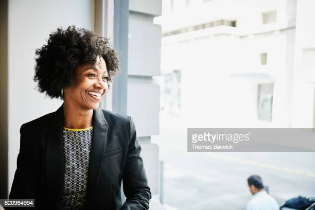 Smiling businesswoman sitting in coffee shop looking out window